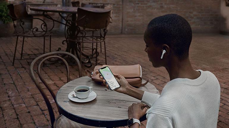 femeie care sta la o masa si priveste la iPhone