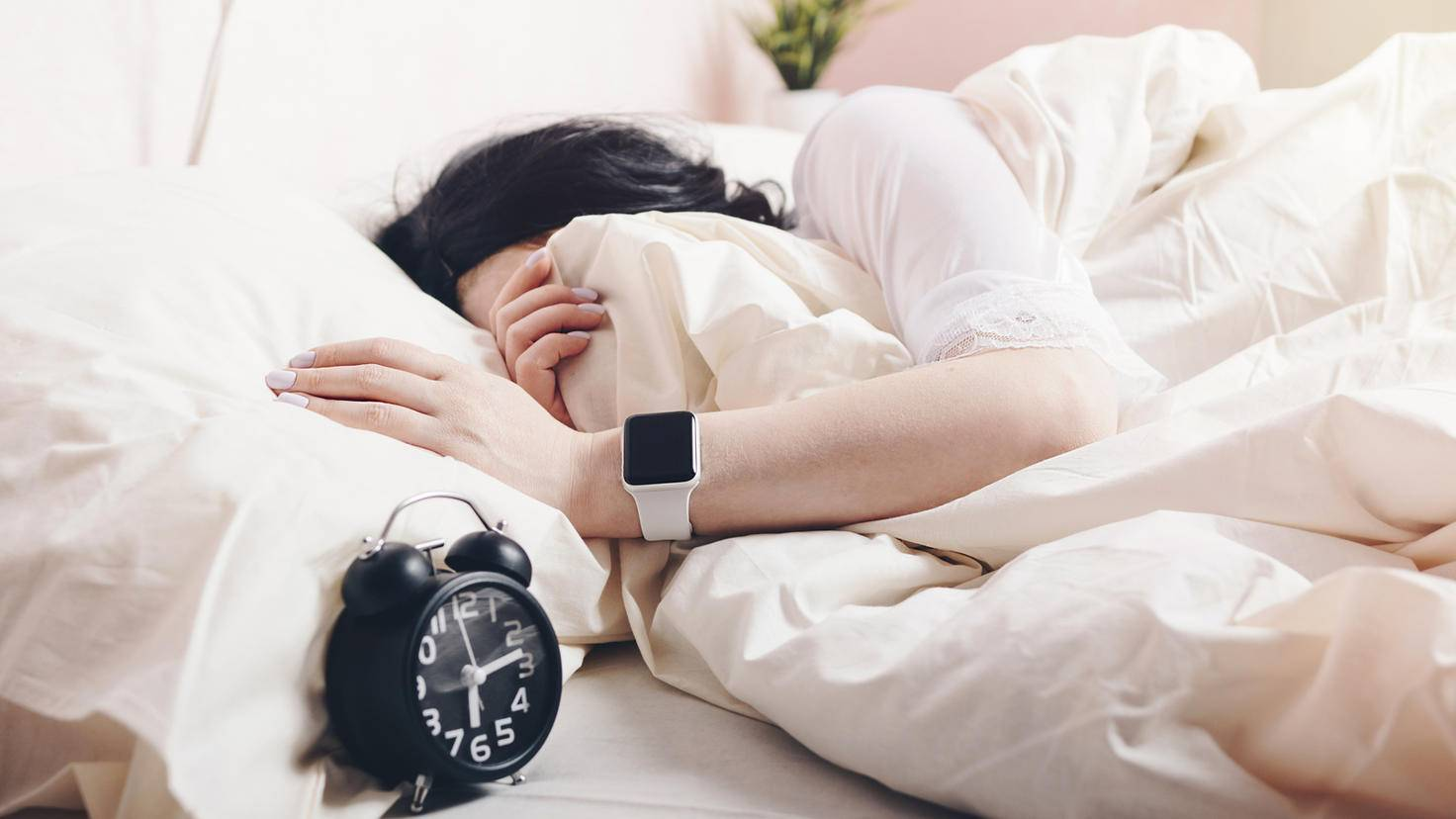 femeie in pat cu apple watch